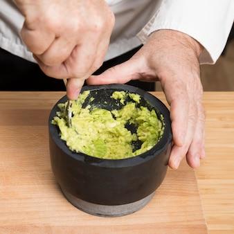Szczegół szef kuchni robi makaronowi z awokado