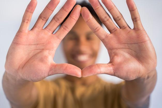 Szczegół szeroko otwartych dłoni razem z przodu. nie do poznania, afroamerykanin człowiek robi kształt znak trójkąta rękami. zatrzymaj rasizm i obejmij różne grupy etniczne.