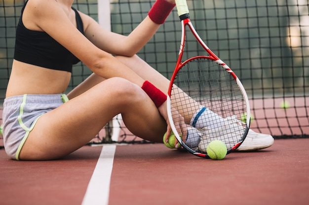 Szczegół tenisista siedzi na podłodze