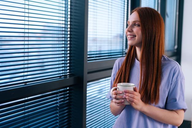 Szczegół twarz szczęśliwa ruda młoda kobieta picia kawy stojący w pobliżu okna po dniu pracy. spokojna uśmiechnięta pani oglądając zachód słońca w pobliżu panoramicznego okna po odpoczynku przy filiżance herbaty.