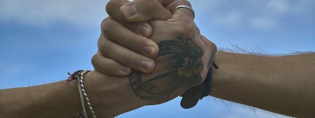 Szczegół uścisku dłoni pod błękitnym niebem, obraz banera z miejscem na kopię
