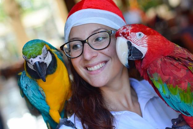 Szczegół uśmiechniętej dziewczyny z papugami na ramionach