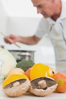 Szczegół warzywa z mężczyzna narządzania jedzeniem w tle