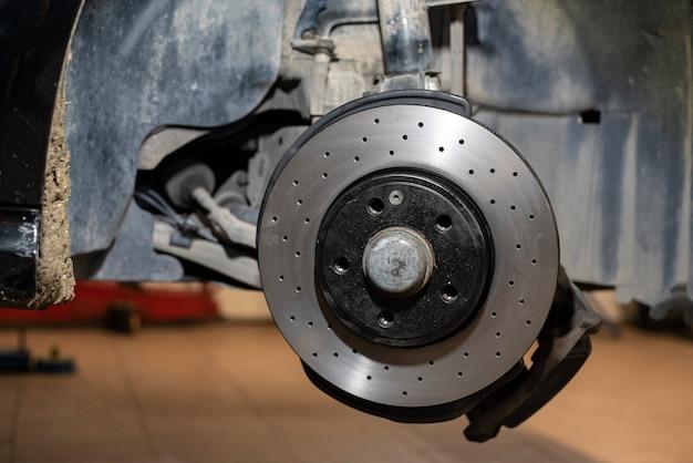 Szczegół wymiany samochodowego hamulca tarczowego w warsztacie mechanicznym