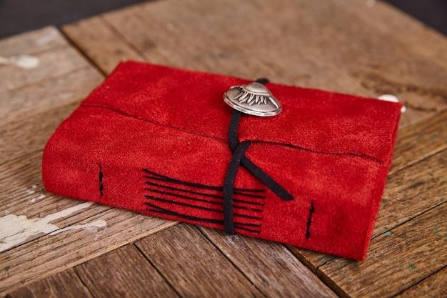 Szczegół zamkniętego czasopisma z czerwonej skóry z czarną nicią na tle drewna