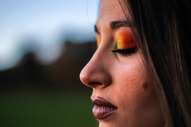 Szczegół zamkniętego oka dziewczyny z kolorowym makijażem na zewnątrz domu