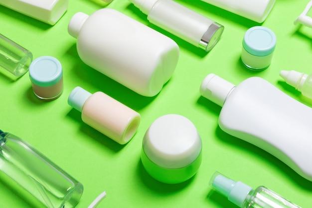 Szczegół zestaw różnych wielkości butelek i słoików na produkty kosmetyczne na zielonym tle. koncepcja pielęgnacji twarzy i ciała z miejsca na kopię.