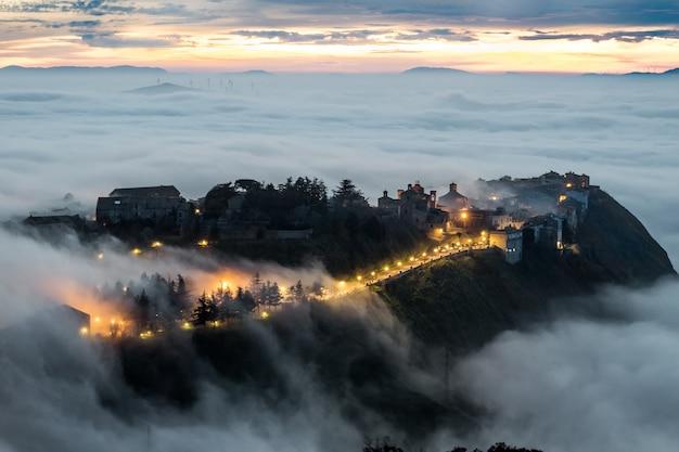 Szczególnie atrakcyjny widok na sycylijskie miasto polizzi generosa, kiedy niska chmura (tzw. maretta
