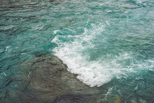 Szczegółowa tekstura turkusowa pędząca powierzchnia wody.