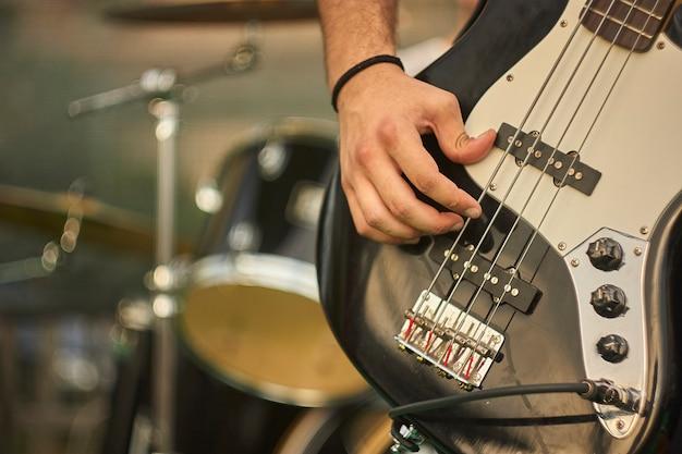 Szczegółowo basista, który gra na basie eacoustica na koncercie muzyki rockowej na żywo.