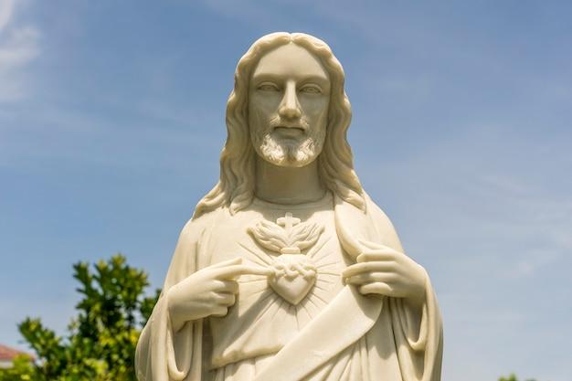 Szczegółowo marmurowy posąg jezusa chrystusa z sercem w świątyni i niebieskim tle nieba w danang, wietnam. ścieśniać