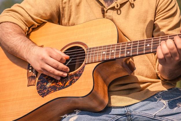Szczegółowo muzyk rockowy grający na gitarze klasycznej