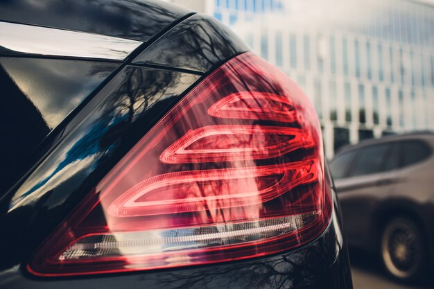 Szczegółowo na tylne światło samochodu. szary samochód w parku. skopiuj miejsce
