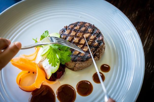 Szczegółowo ręce osoby jedzącej filet z mięsa z warzywami z widelcami w restauracji.