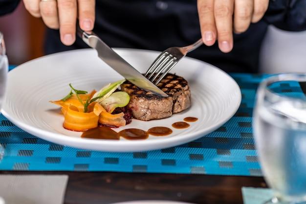 Szczegółowo ręce osoby krojącej filet z mięsa garniru z warzywami widelcami w restauracji.
