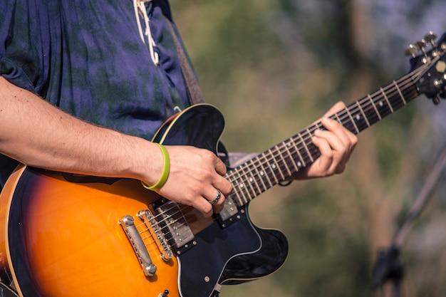 Szczegółowo rocker grający na gitarze elektrycznej na koncercie na żywo.