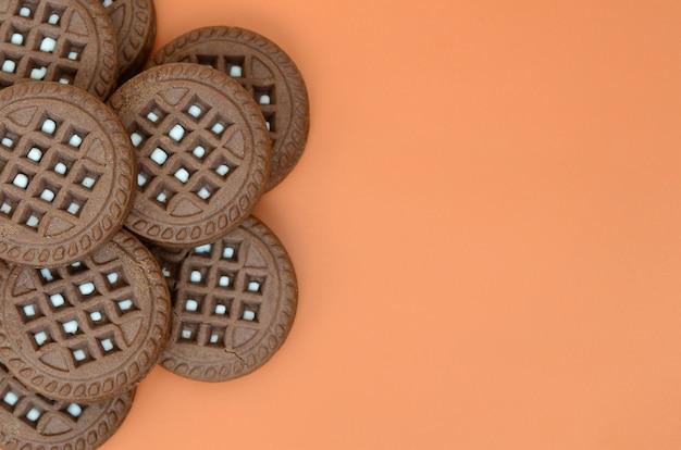 Szczegółowy obraz ciemne brązowe okrągłe ciasteczka kanapkowe z nadzieniem kokosowym na pomarańczowej powierzchni.