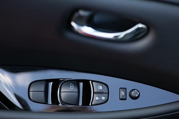 Szczegółowy opis przycisków kontrolujących okna w samochodzie. detale wnętrza samochodu z klamką z elementami sterowania szyb i elektrycznymi lusterkami. panel sterowania okien i lusterek na drzwiach kierowcy