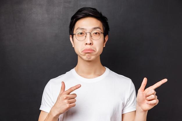 Szczegółowy portret pod wrażeniem azjatyckiego mężczyzny w białej koszulce w okularach, bielmik i wyglądający aparat z aprobatą, wskazujący palcami na naprawdę fajny niesamowity produkt, zgadzam się z tobą,