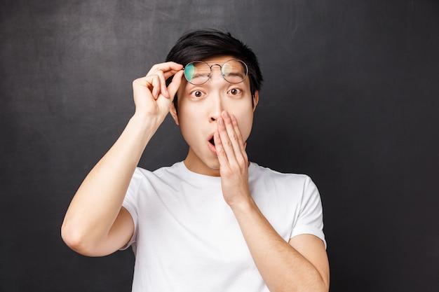 Szczegółowy portret pod wrażeniem, zdziwionego azjatyckiego faceta, zdejmowanie okularów ze zdumienia, zakrywanie otwartych ust, sapanie i powiedzenie wow zachwycony, zaskoczony widokiem czegoś naprawdę fajnego,