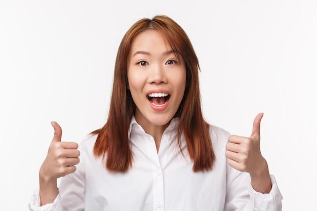 Szczegółowy portret wspierającej ślicznej, pozytywnej dziewczyny z azji pokazuje kciuki do góry i uśmiecha się rozbawiony, wyraża podekscytowanie i satysfakcję, jak i zatwierdza wielki wybór, mówi dobrą robotę,