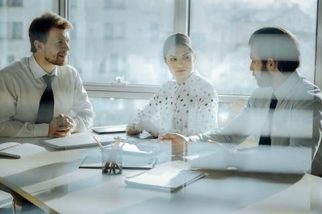 Szczegółowy raport. dwóch młodych kolegów siedzi przy stole w biurze swojego szefa i raportuje go, podczas gdy on zwraca na niego uwagę