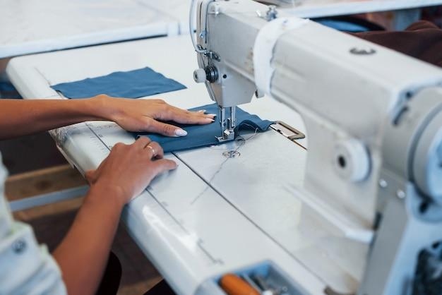Szczegółowy widok kobiety krawcowej szyje ubrania na maszynie do szycia w fabryce.