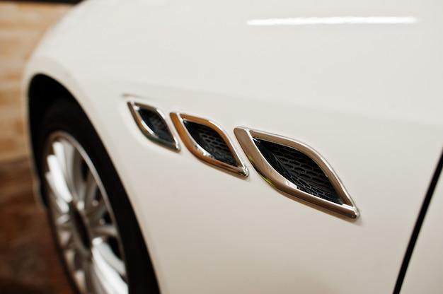 Szczegóły białego nowego luksusowego samochodu sportowego w garażu detailingowym.