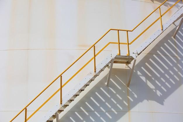 Szczegóły białych zbiorników oleju w zbiorniku z żelaznymi schodami cień.