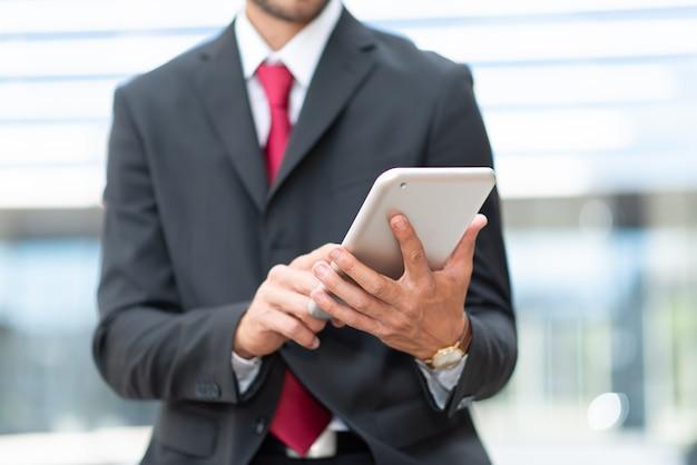 Szczegóły biznesmena za pomocą swojego cyfrowego tabletu