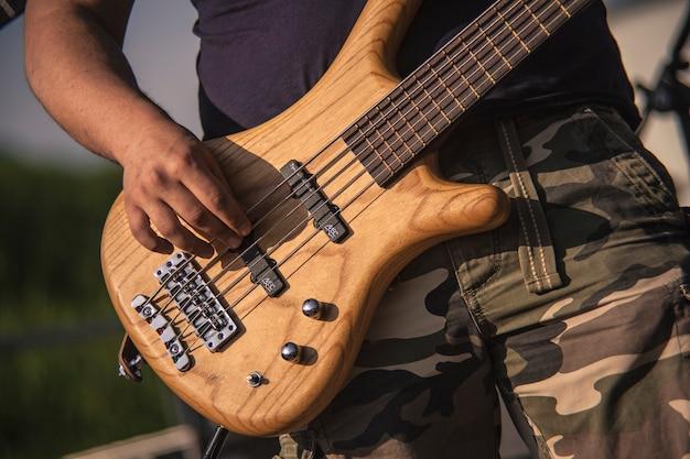 Szczegóły dłoni podczas grania na drewnianym basie akustycznym na koncercie rockowym