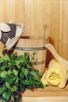 Szczegóły dotyczące wnętrz fińska sauna łaźnia parowa z tradycyjnymi akcesoriami do sauny umywalka brzozowa miotła szufelka filcowa czapka ręcznik