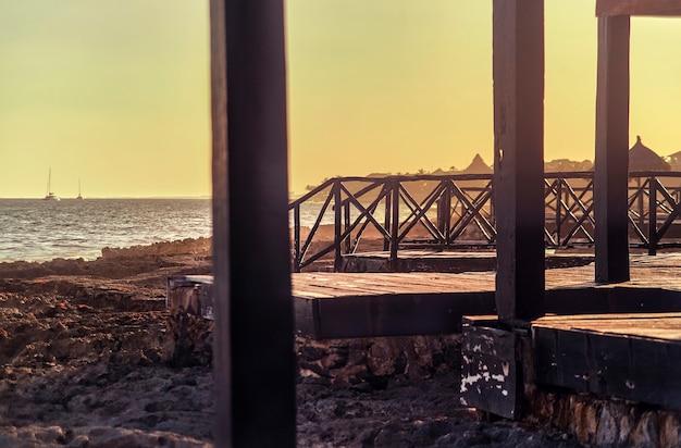 Szczegóły drewniane molo z widokiem na piękną plażę puerto aventuras w meksyku na riwierze majów o zachodzie słońca.
