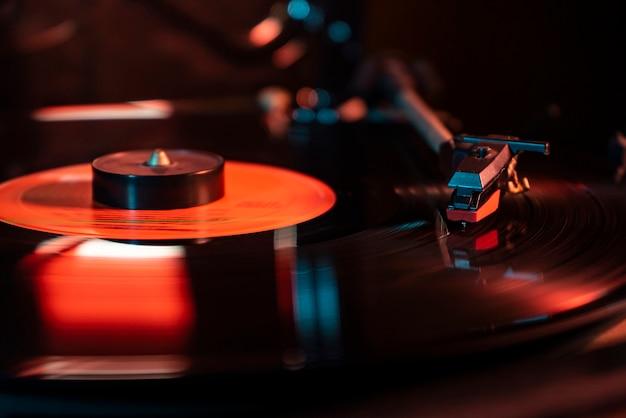 Szczegóły igły na płycie winylowej na gramofonie, obraz w słabym świetle z odbiciem