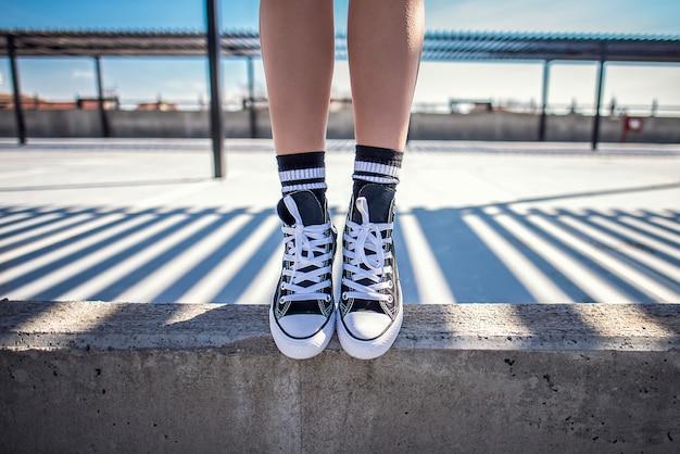 Szczegóły kobiecych nóg stojących na konkretnej półce w jej klasycznych sneakers