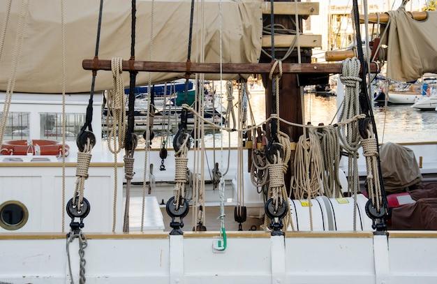 Szczegóły łodzi i roaps w porcie w barcelonie na morzu śródziemnym w słoneczny dzień. biały jacht znajduje się w hiszpańskim porcie w barcelonie na początku lata.