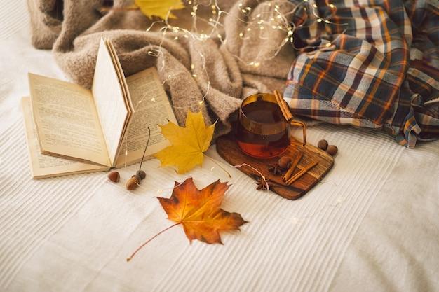 Szczegóły martwej natury w domowych swetrach i filiżance herbaty z jesiennym wystrojem i książkami czytają resztę
