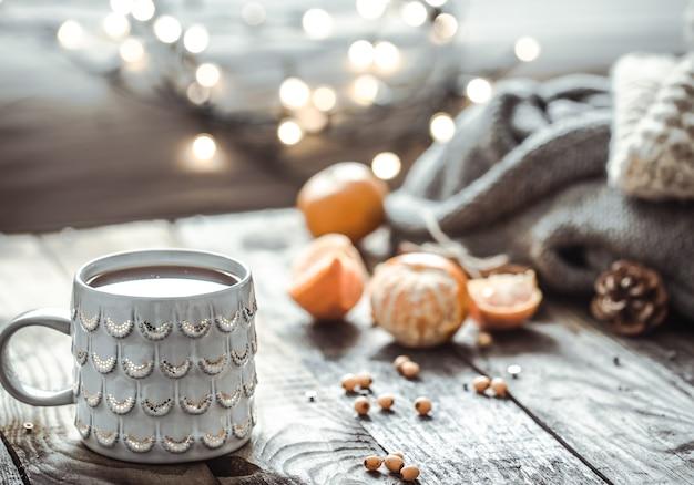 Szczegóły martwej natury w salonie wnętrza domu. piękny kubek herbaty z mandarynkami i swetry na podłoże drewniane. przytulna koncepcja jesień-zima