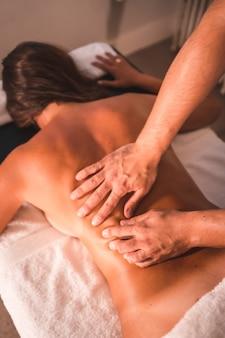 Szczegóły masażu pleców fizjoterapeuty młodej kobiety leżącej na stole. fizjoterapia, osteopatia, masaż relaksacyjny, film z zabiegu na plecach