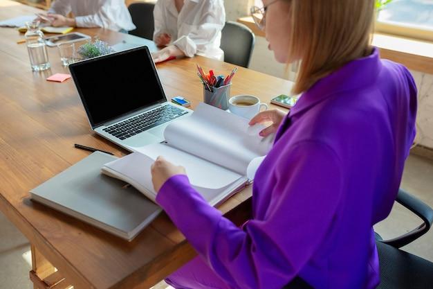 Szczegóły. młoda biznesowa kaukaski kobieta w nowoczesnym biurze z zespołem.