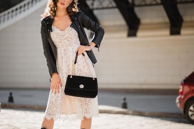 Szczegóły mody z bliska atrakcyjnej kobiety spacerującej po ulicy w modnym stroju trzymającej torebkę na sobie czarną skórzaną kurtkę i białą koronkową sukienkę w stylu wiosenno-jesiennym