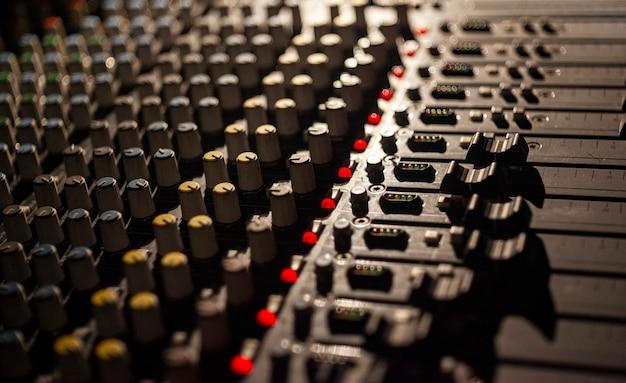 Szczegóły potencjometrów i elementów sterujących wielokanałowego miksera audio używanego do zarządzania koncertem
