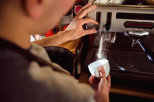Szczegóły przygotowywa świeżą kawę espresso na przemysłowej browarnianej maszynerii barista.