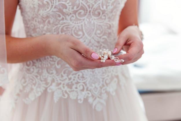 Szczegóły ślubu i akcesoria, panna młoda wkłada perłowy kolczyk