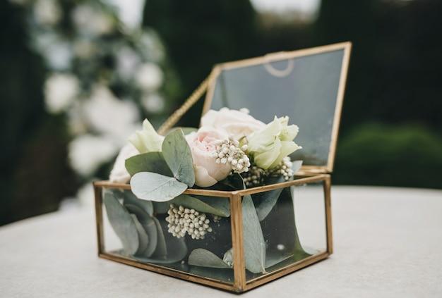 Szczegóły ślubu. szklane pudełko ze świeżymi kwiatami, różami i zielenią