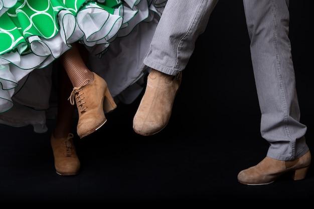 Szczegóły stóp tancerzy flamenco na czarnym tle.