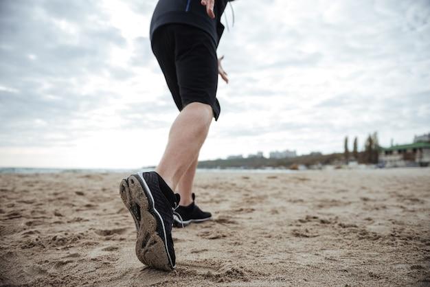 Szczegóły stóp z tyłu na przyciętym obrazie na plaży