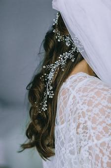 Szczegóły sukni ślubnej. bliska bez twarzy dziewczyny w pięknej białej sukni ślubnej. akcesoria panny młodej. gorset, welon i koronka. poranek panny młodej.