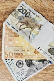 Szczegóły w 200 realach, 100 dolarach, banknotach 50 euro brazylia, usa, europa fotografia pieniądze.