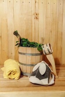 Szczegóły wnętrza sauna fińska łaźnia parowa łaźnia z tradycyjnymi akcesoriami do sauny umywalka brzozowa miotła szufelka filcowa czapka ręcznik